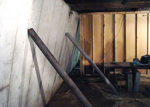 A severely tilting foundation wall propped up by steel beams in Upper Darby.